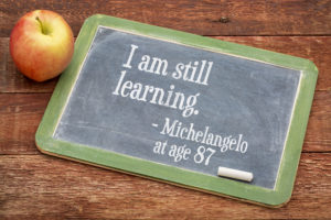 I am still learning - Michelangelo at age 87 - continuous education concept on a slate blackboard against red barn wood